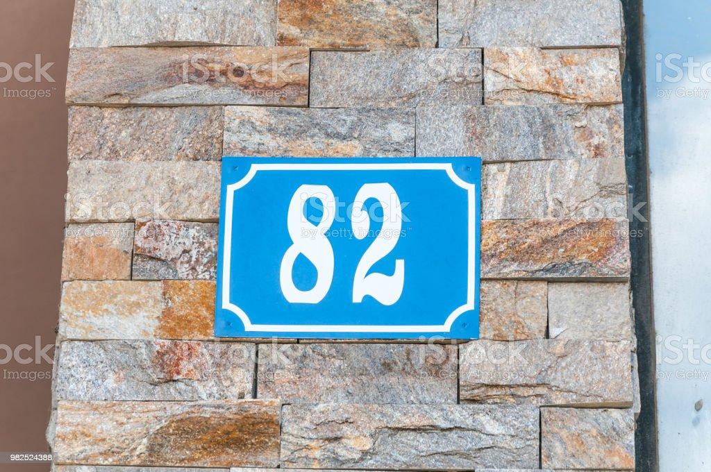 Endereço de casa vintage azul antigo metal placa 82 na fachada de tijolo decorativo da parede exterior do edifício residencial lado da rua - foto de acervo
