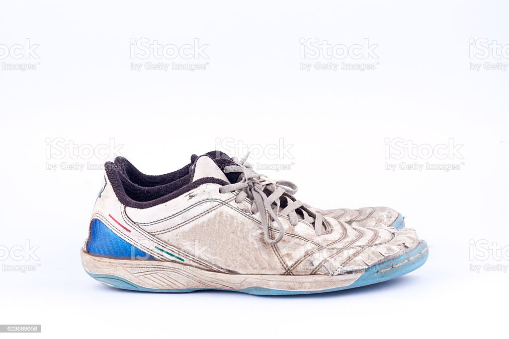 Old blue worn out futsal sports shoes  on white background stock photo