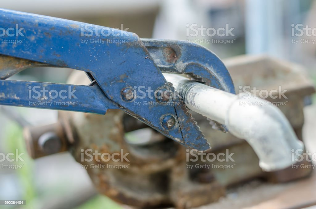 Old blue wrench unwind elbow from pipe, close up stock photo