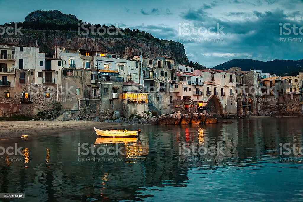 old boat and houses in Cefalu at dusk stock photo
