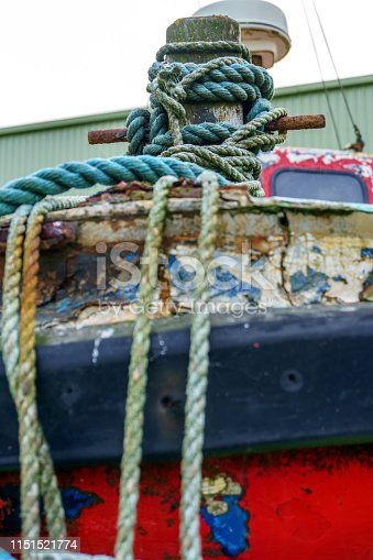 Boats moored in harbour at Kilmore Quay in Ireland focus on the rope