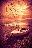 Old Boat on Lake at Sunset. Toned Image.