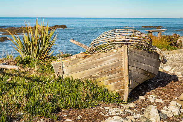 Old boat with a lobster trap on a seashore stock photo