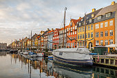 Nyhavn, Copenhagen, Denmark, December 16, 2020. Old boats and houses in the winter sun in the center of Copenhagen at one of the most popular tourist spots during summertime