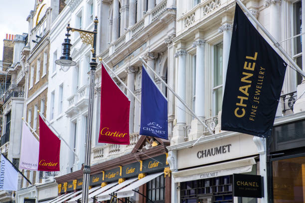London, UK - August 13, 2019: Old Bond street view with flags of famous fashion houses. London, UK - August 13, 2019: Old Bond street view with flags of famous fashion houses. Bond Street is a major shopping street in the West End of London for luxury designer brands mayfair stock pictures, royalty-free photos & images