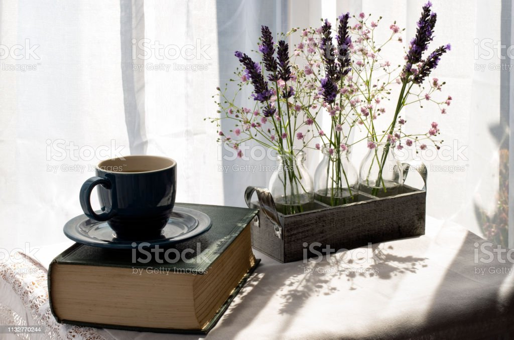 Old Book and a coffee cup with flowers stock photo