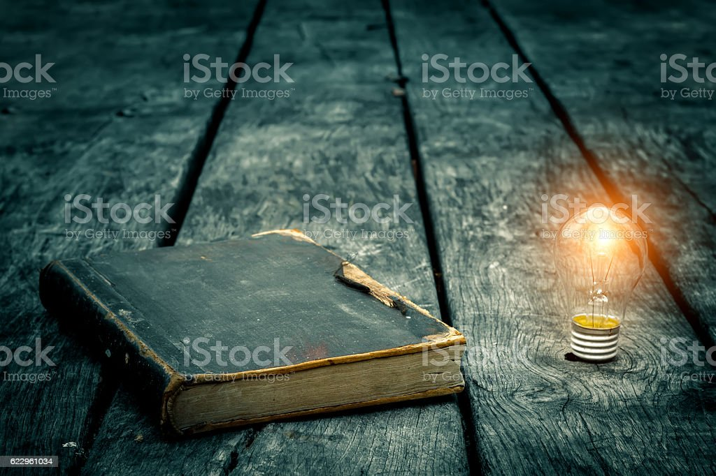 Old book and burning light bulb on a wooden table - foto de stock