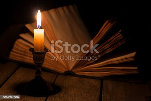 istock Old book and candle 850259830