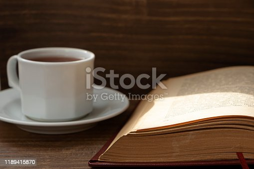 Hot tea, vintage book on wooden background.