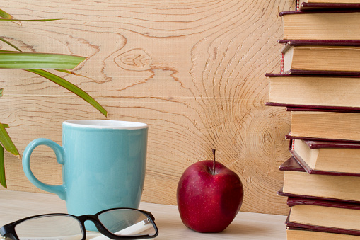 old books, glasses, apple and coffee with wooden on background.