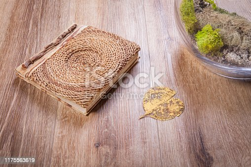 Old book and golden leaf on a wooden floor