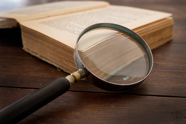 Old book and magnifying glass stock photo