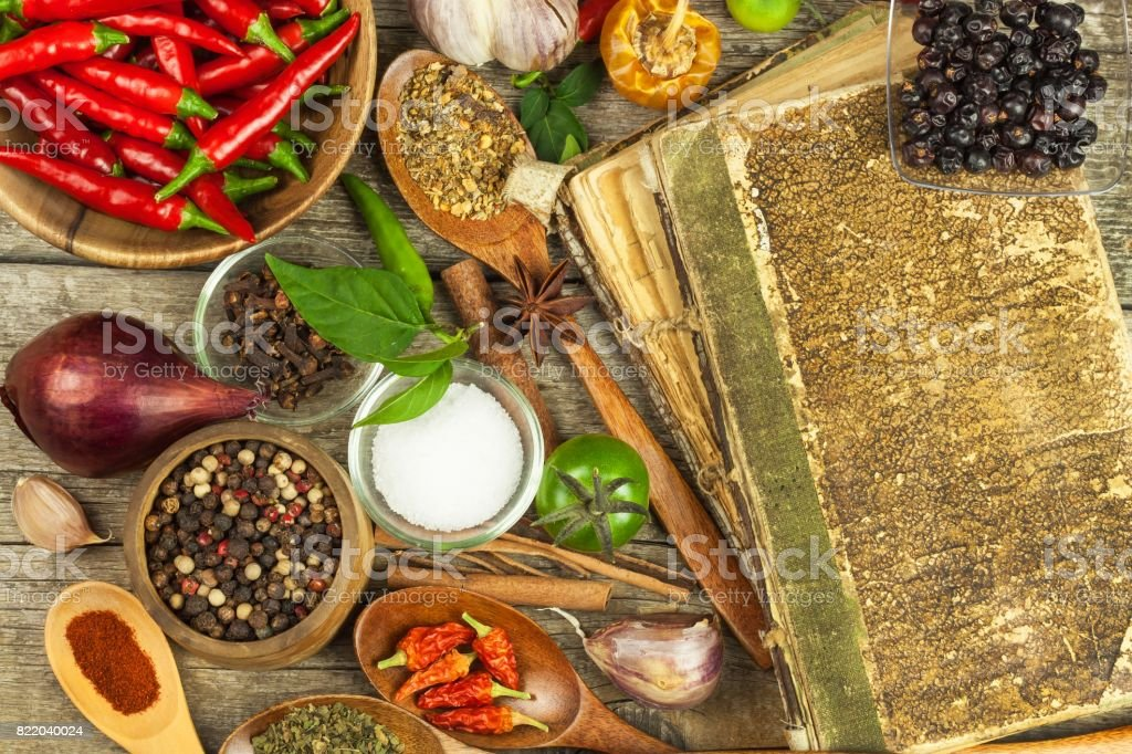 Old book of cookery recipes. Culinary background and recipe book with various spices on wooden table. Old book of cookery recipes. Culinary background and recipe book with various spices on wooden table Backgrounds Stock Photo
