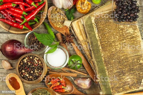 Old Book Of Cookery Recipes Culinary Background And Recipe Book With Various Spices On Wooden Table Stock Photo - Download Image Now