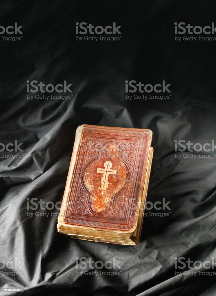 Old book on black background. Ancient christian Bible. Antique slavonic Holy Scripture book. Orthodox cross on bible cover. stock photo