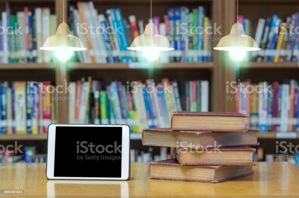 old book on the desk in library with tablet and Luxury lighting decoration stock photo