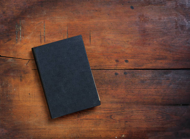 Old book on wooden background Old book on wooden background - copy space hardcover book stock pictures, royalty-free photos & images