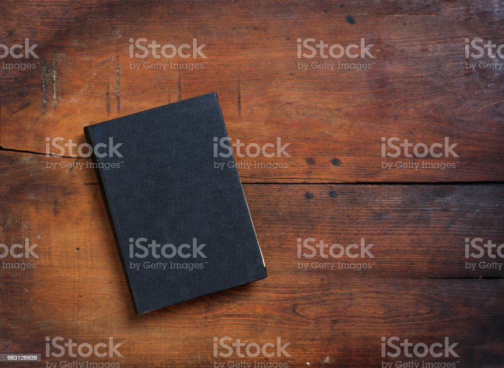 Old book on wooden background stock photo