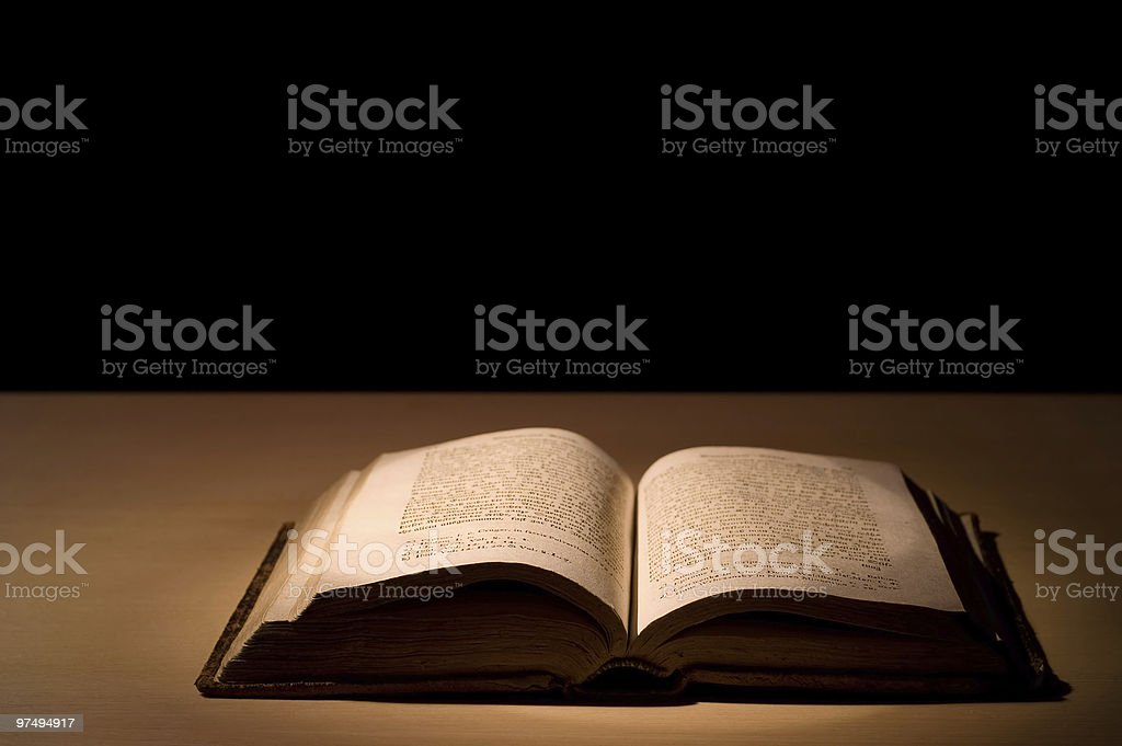 Old book open on wooden surface isolated on black background royalty-free stock photo
