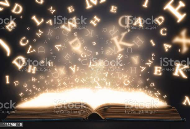 Old Book Open With Flying Magic Letters Stock Photo - Download Image Now