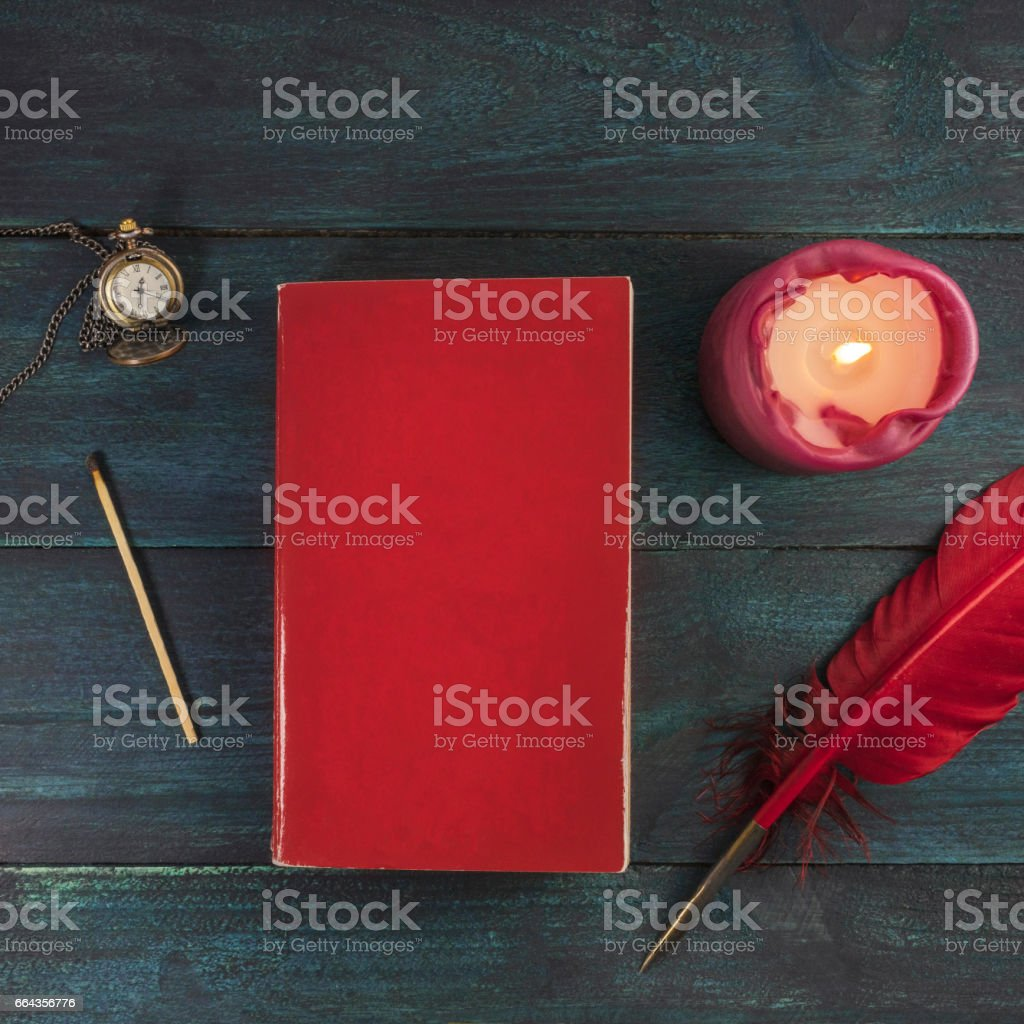 Old book, watch, candle, and quill pen with copyspace stock photo