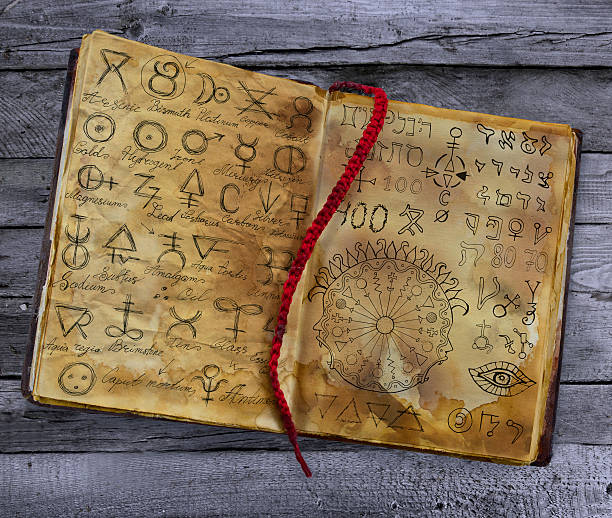 Old book with alchemic symbols lying on the wooden table stock photo
