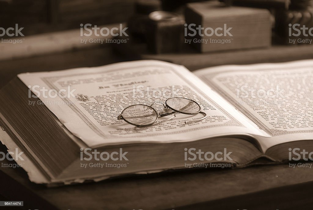Old book with an antique reading glasses stock photo