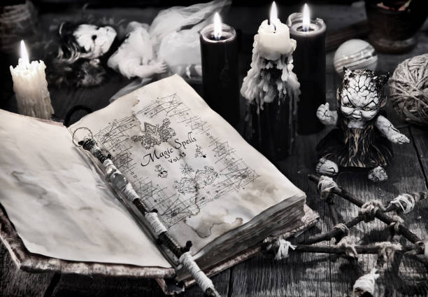 Old book with black magic spells, scary doll, black candles and pentagram stock photo