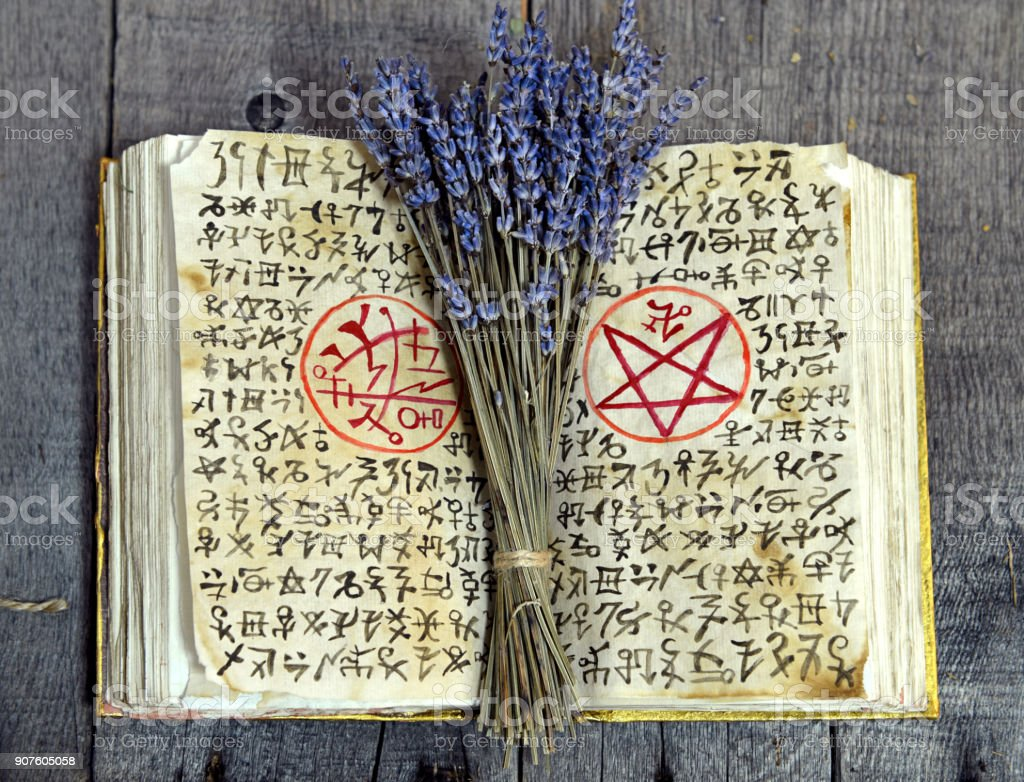 Old book with black magic symbols and lavender bunch on witch table stock photo
