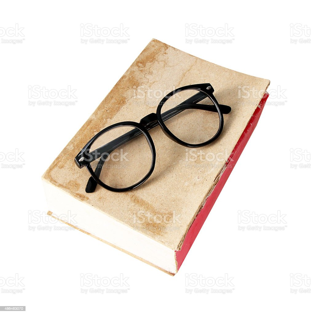 Old book with glasses on white background stock photo