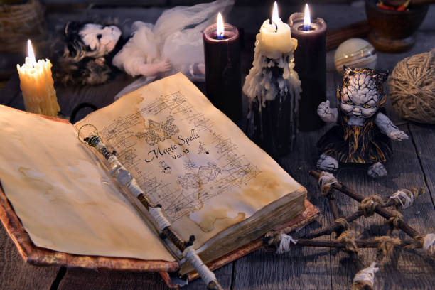 Old book with magic spells, scary doll, black candles and pentagram on witch table stock photo