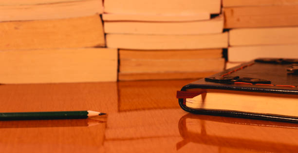 old books and a pencil on the wooden table stock photo