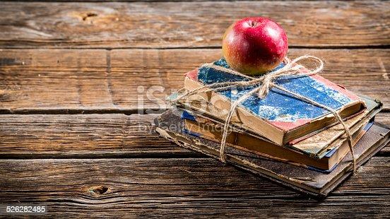 istock Old books and apple on school desk 526282485