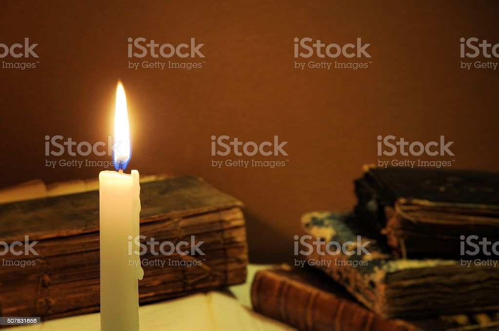 Old books and candle. Knowledge concept. stock photo