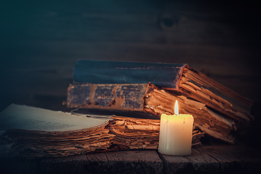 istock Old books and candle. 918381280