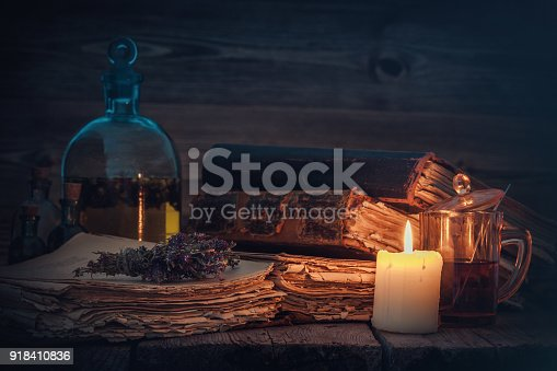 Old books and candle, tincture or potion bottle, glass of beverage and bunch of dry healthy herbs.