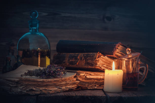 Old books and candle, tincture or potion bottle, glass of beverage and bunch of dry healthy herbs. stock photo