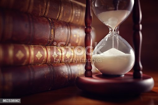 istock Old books and hourglass 862338562