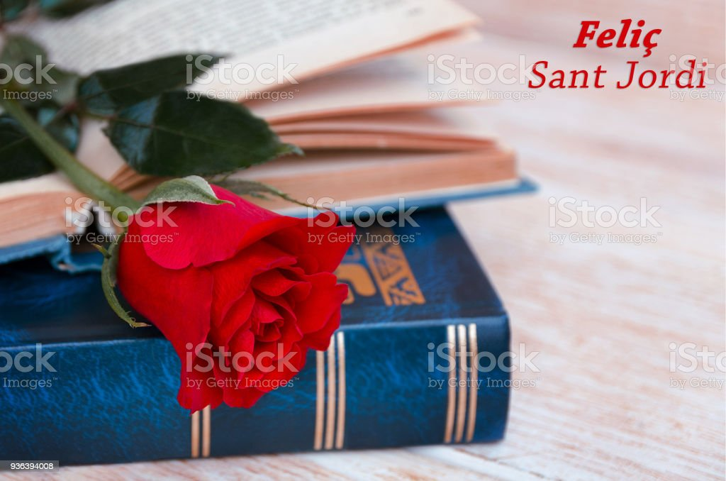 Old books and red rose, traditional gift for Sant Jordi, Catalunya's version of Valentine's day, celebrated on 23rd of April. Phrase Happy Saint Georges in Catalan stock photo
