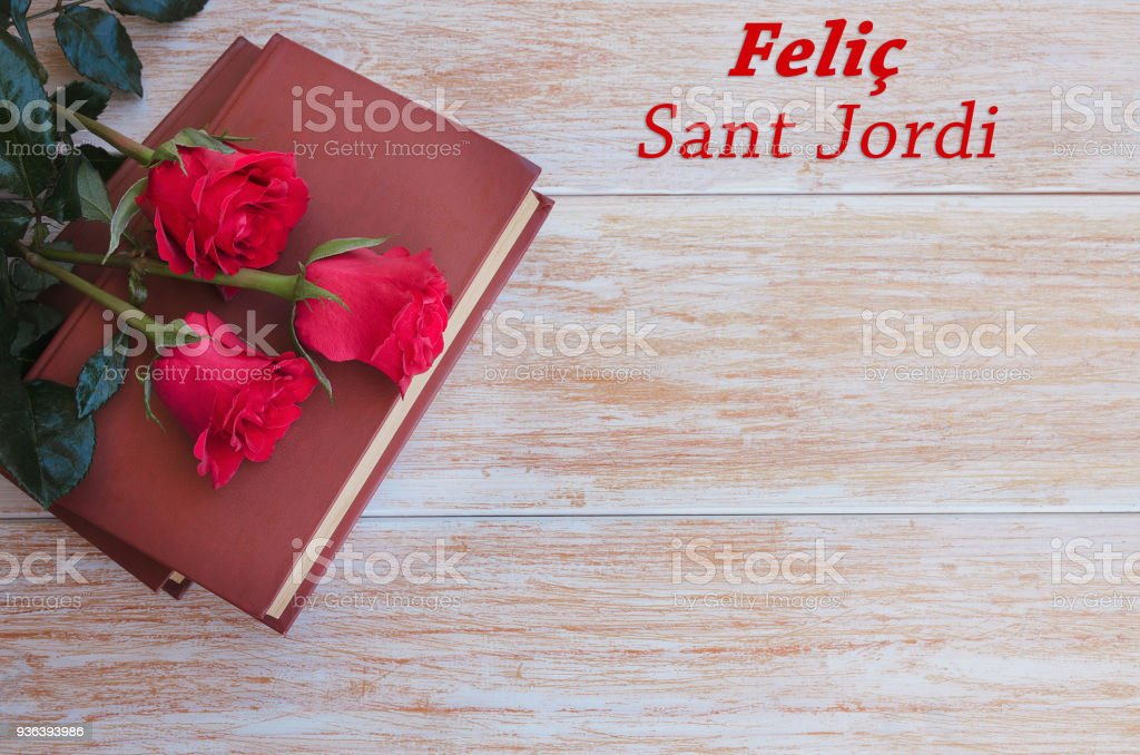 Old books and red rose, traditional gift for Sant Jordi, the Saint Georges Day. Catalunya's version of Valentine's day.Phrase Happy Sant Jordi in catalan stock photo