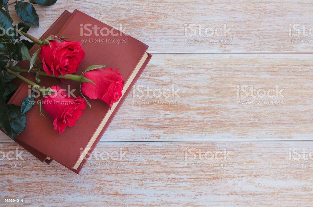 Old books and red rose, traditional gift for Sant Jordi, the Saint Georges Day. Catalunya's version of Valentine's day. stock photo