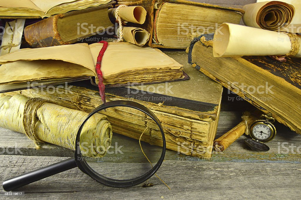 Vintage still life with pile of old books, pocket watch and enlarging...
