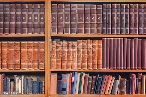 Old volumes and collections of books on a set of shelves.