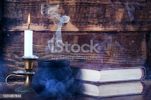 istock Old books of magic and witch pot with smoke and candle 1024387844