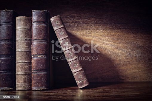 istock Old books on a library shelf background 853912164