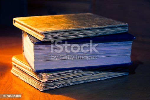 537881816 istock photo Old books on a table in the dark living room 1070435468