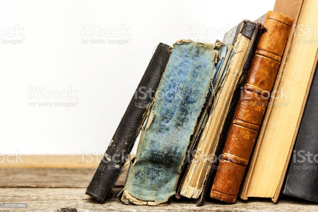 Old books on a wooden shelf on a white background. Study of old...