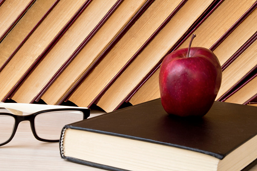 old books, glasses and red apples on wooden shelf.