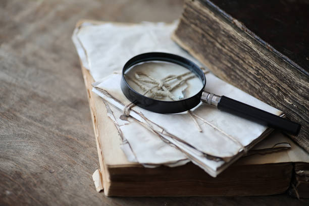 Old books on a wooden table and magnifier Old books on a wooden table and glass magnifier detective stock pictures, royalty-free photos & images