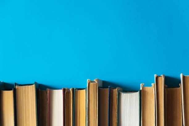 libros antiguos sobre fondo azul - biblioteca fotografías e imágenes de stock